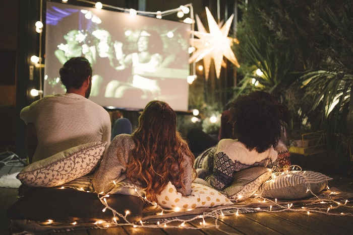 friends outdoors watching a movie on a big screen in a garden