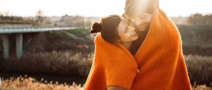 couple outdoors cuddling and smiling under an orange blanket