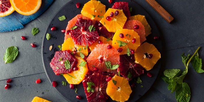 winter fruits different types of oranges on a dark plate with a dressing