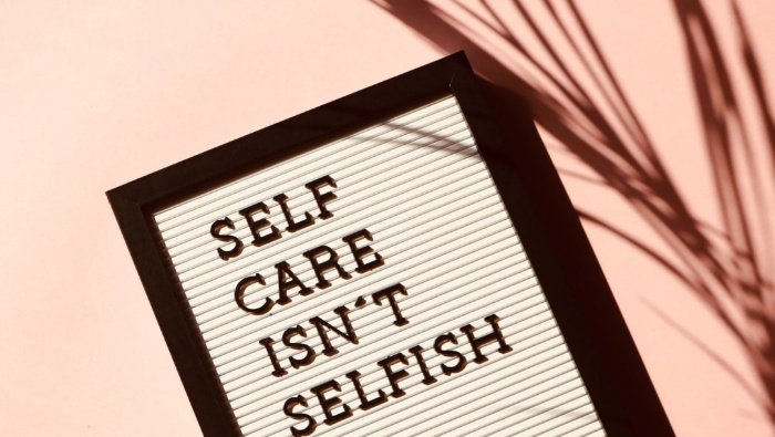 note in a black frame self care isn't selfish on a pink background