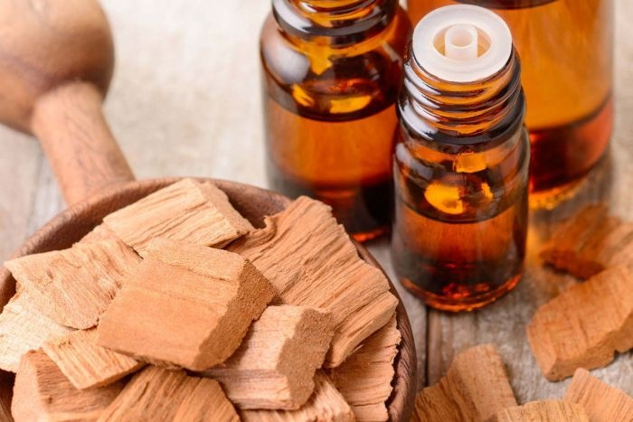 pieces of sandalwood and dark bottles with essential oil