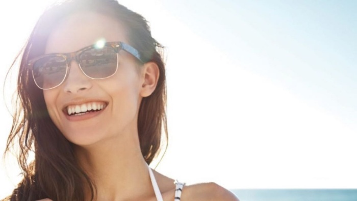 woman with her glasses on smiling in a sunny weather
