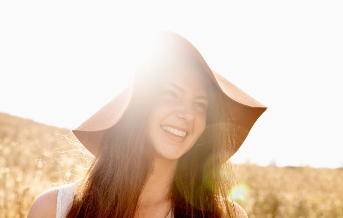 girl smiling outside in the sun wearing a wide hat