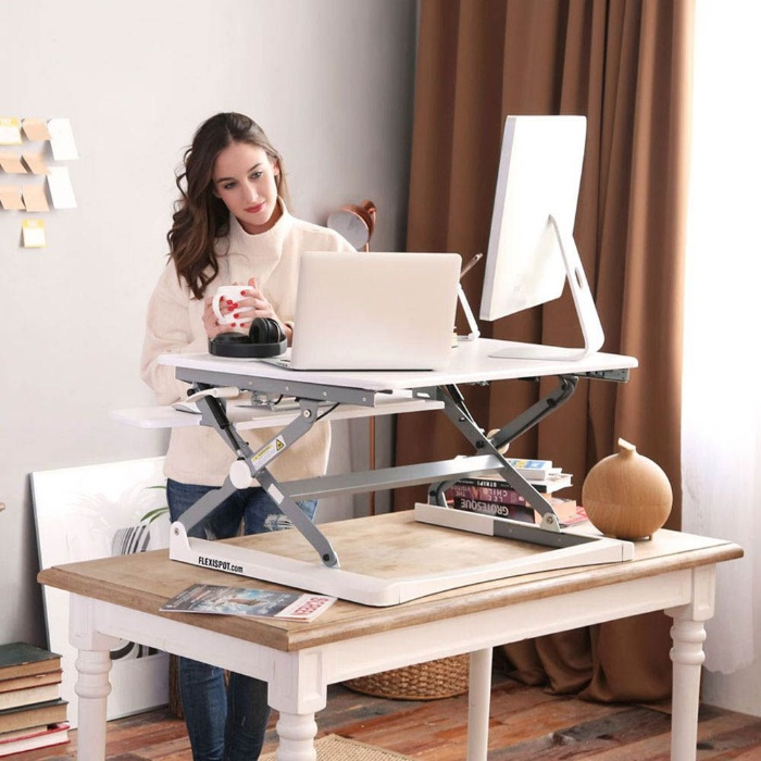 standing desk woman in her home office holding a mug with computers