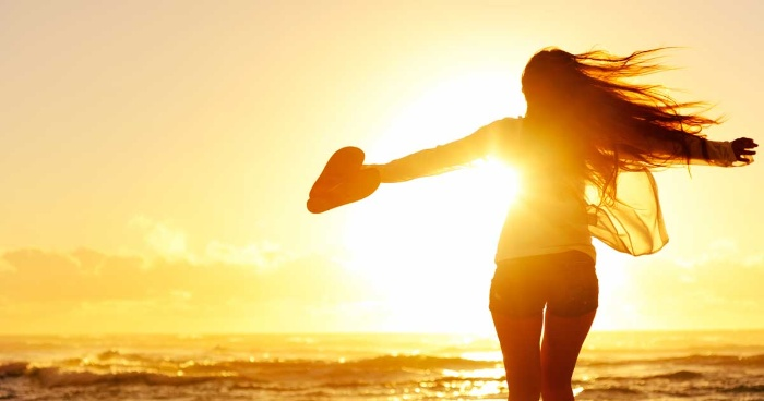 woman running towards the sun and sea holding her flip flops