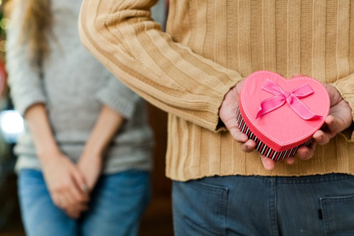 Valentine's day gift man holding a heart gift for a woman