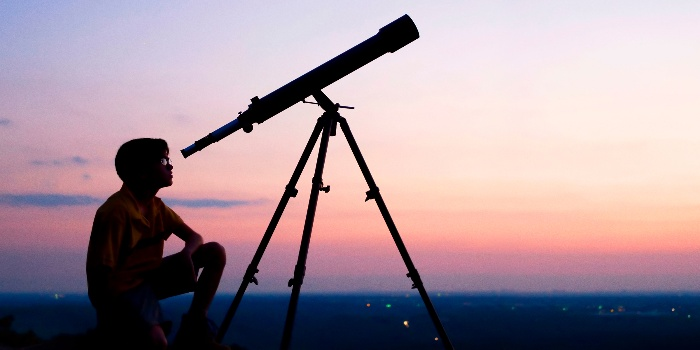 person behind a telescope watching the stars in the night sky