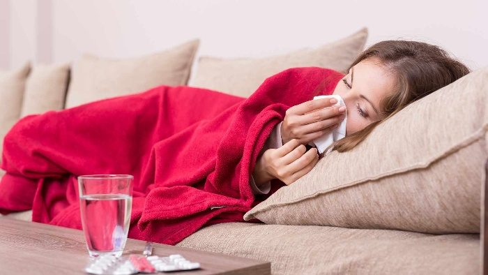 woman lying on a sofa covered with a red blanket sneezing