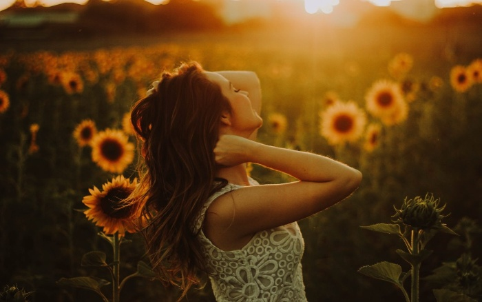 new year resolutions woman in a sunflower field watching the sunrise