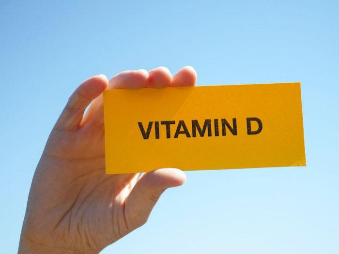 hand holding a yellow vitamin d sign on a blue background