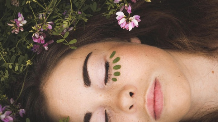 woman lying on the grass flowers around with green leaves under her eyes