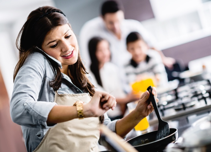 woman multitasking cooking speaking on the phone and checking her watch