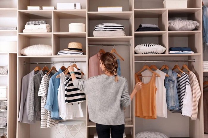 woman organizing her clothes in front of a large wardrobe
