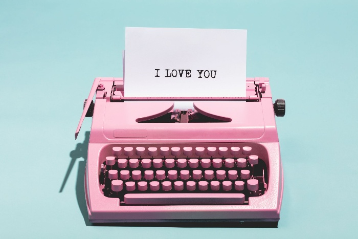 a pink typewriter with a white paper writing I love you