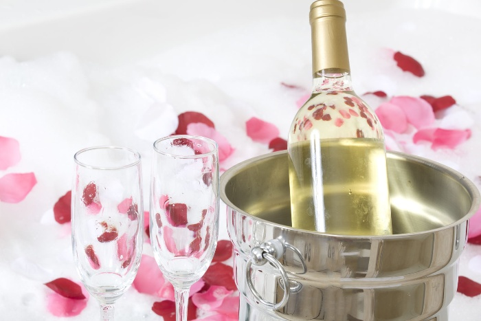 love and romance bubbly and chocolate champagne bottle in a cooler with glasses and rose petals