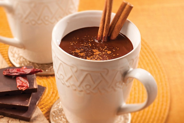 cinnamon and cocoa hot beverage in a white retro mug on a table with chocolate bars