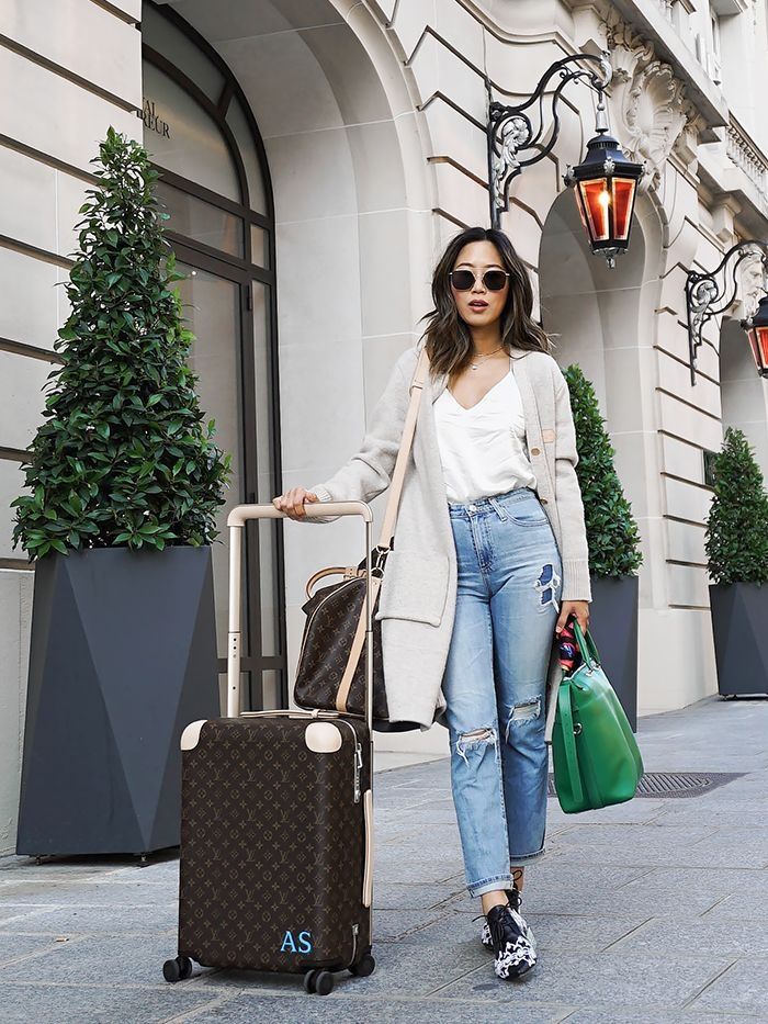 girl on a trip with her suitcases sunglasses and jeans on a street