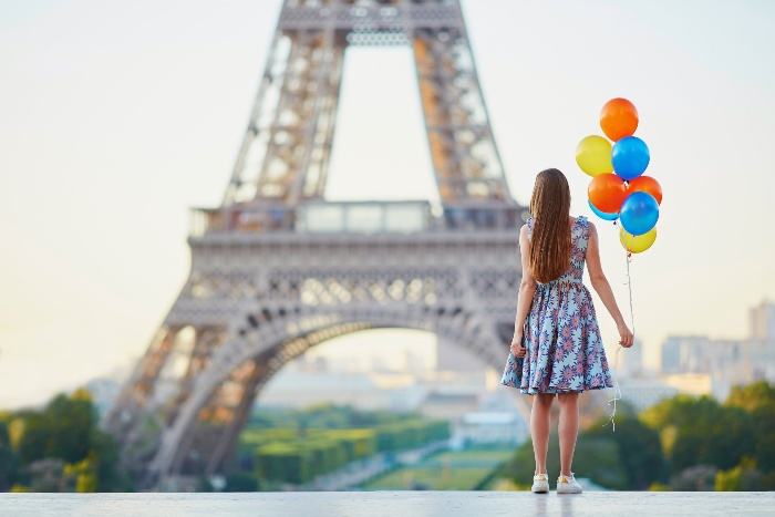 girl in a dress in front of the eiffel tower in Paris with colorful balloons in her hand