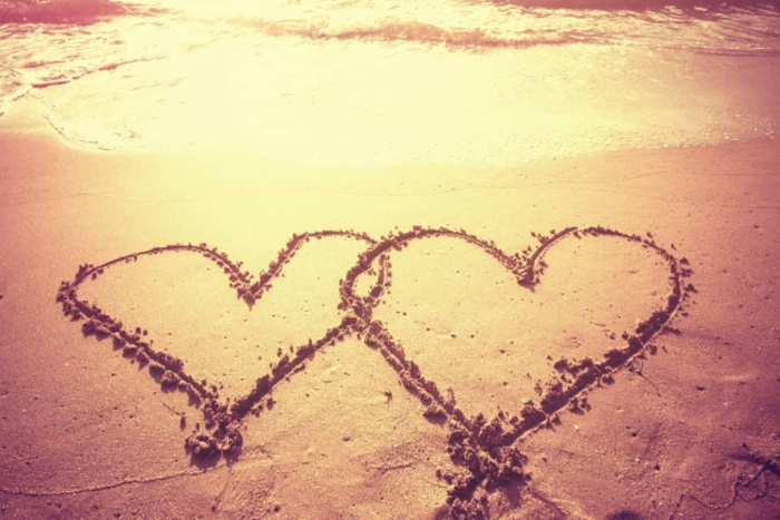 hearts drawn on a beach in the wet sand