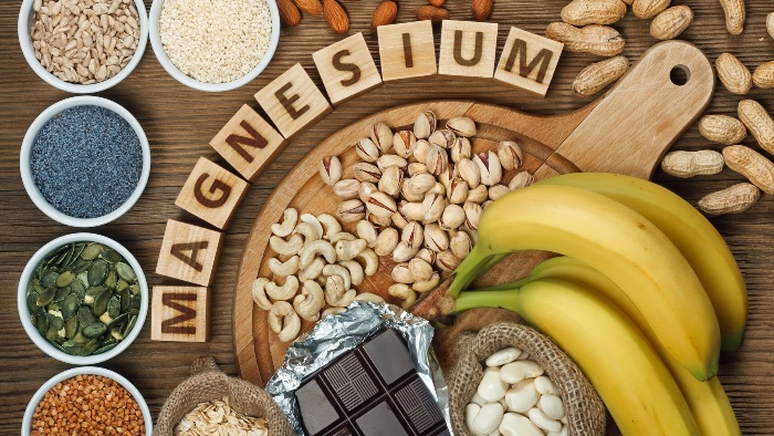 magnesium foods nuts bananas chocolate and other seeds magnesium written on wooden blocks