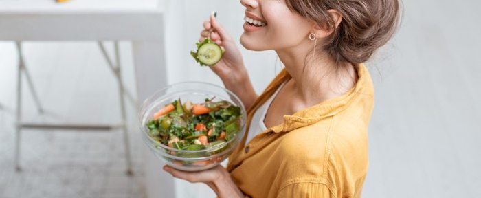 magnesium supplement woman smiling and eating a salad with a fork