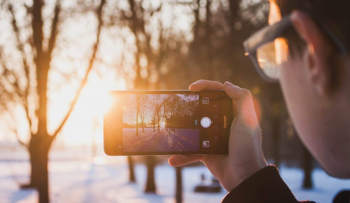 amazing photos with your phone boy with glasses taking photos outdoors at sunset