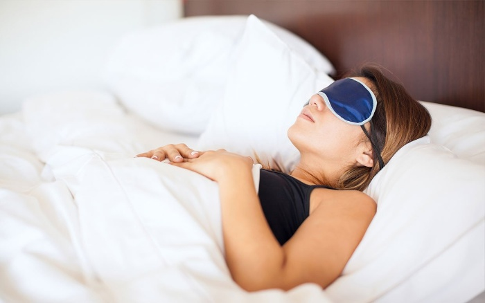 relaxation techniques for good sleep woman with an eye mask laying in bed