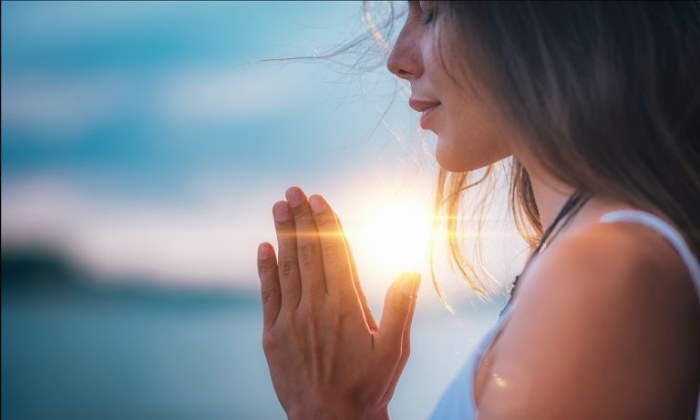 relaxation technique woman praying with her palms together at sunset