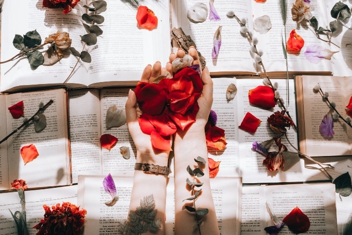 woman holding rose petals in her hands on the background of open books