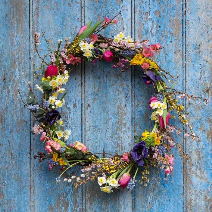 spring wreath on a bright blue door fresh flowers