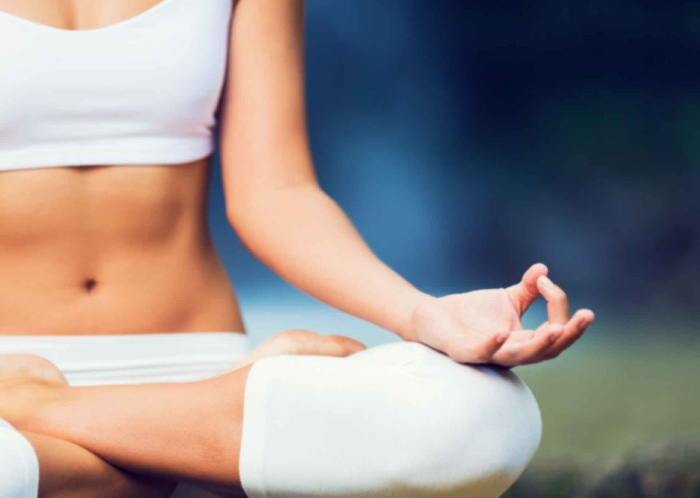 stress relief woman in a yoga pose with her legs crossed and her hands in a mudra