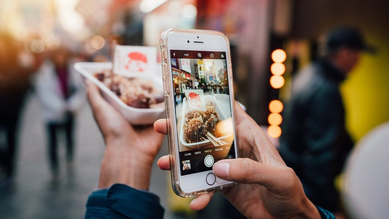 man taking a photo of their food with their phone on the street