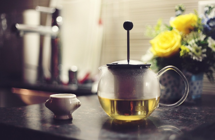 warm glass tea pot with a little cup on a kitchen table with flowers