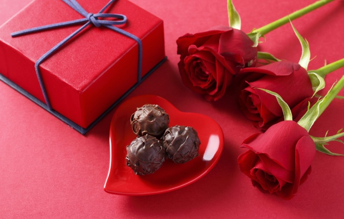 valentine day red wrapped gift chocolate candy in a heart shape plate and three red roses