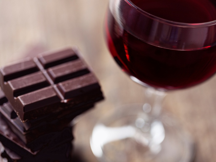 wine and chocolate on a wooden table bars of chocolate and a glass of red wine