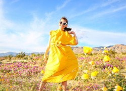 Woman in yellow dress standing surrounded by wildflowers