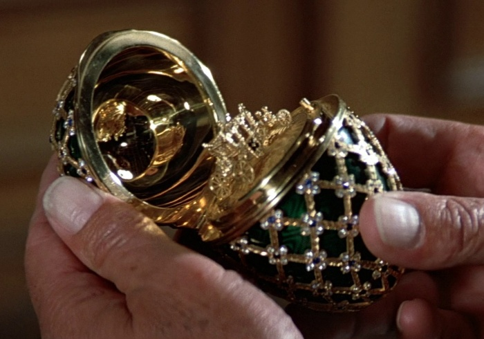 A hand holding an open a black and gold Faberge egg