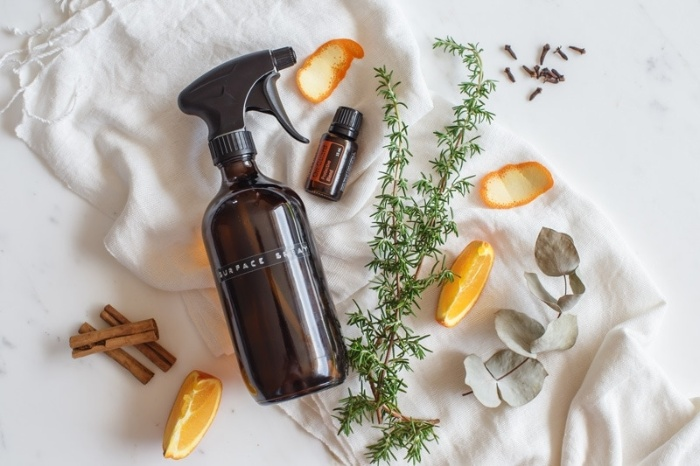 all purpose cleaner in a glass spray bottle with pieces of cinnamon orange slices and herbs