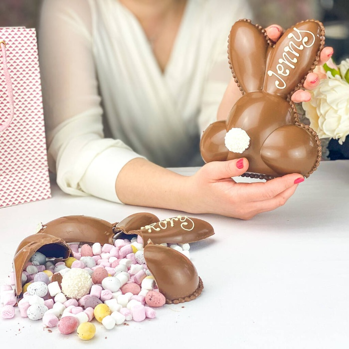 woman holding a hollow easter bunny full of candy