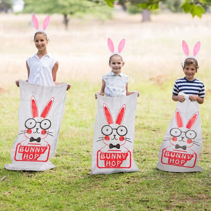 bunny hop race three children dressed like bunnies on a green lawn in bunny sacks ready to compete