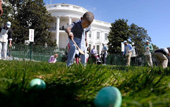 children chasing eggs on the lawn in front of the white house