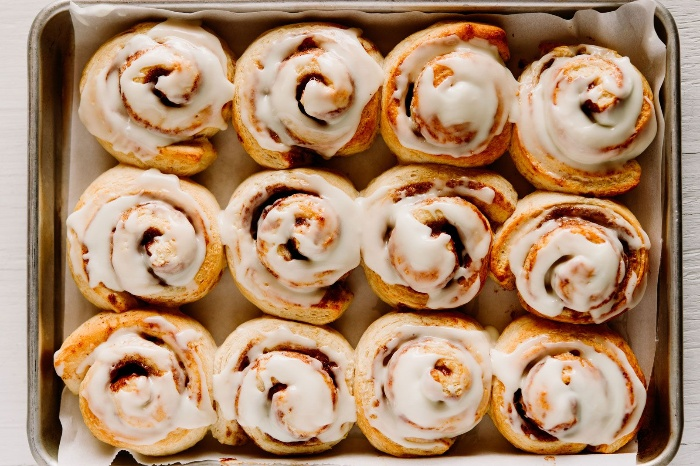 cinnamon rolls in a baking tray with white icing on top