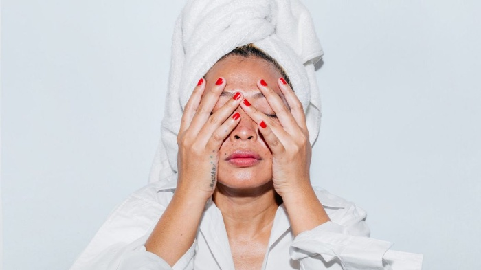 clean your skin woman with a white towel on her head holding her face with two hands