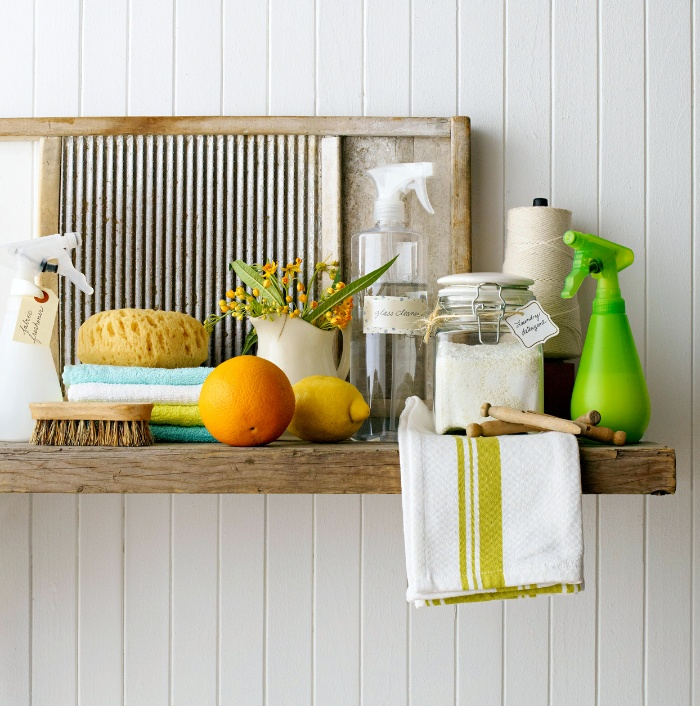 cleaning supplies on a wooden shelf on a white wall brushes towels lemon orange and sprays