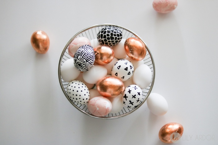 a metal bowl full with modern eggs decorated with metalic and geometrical black and white patterns
