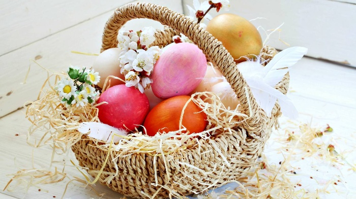 easter basket full of colorful eggs and blossoming spring branches