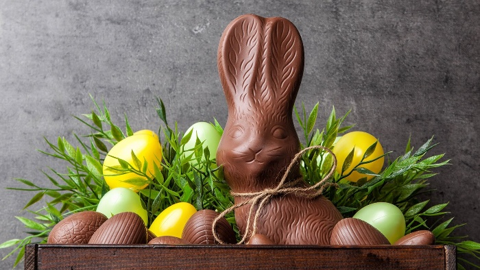 easter chocolate bunny and eggs in a colorful arrangement with green leaves