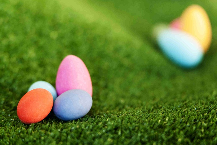 colored easter eggs for easter bowling game on a green lawn