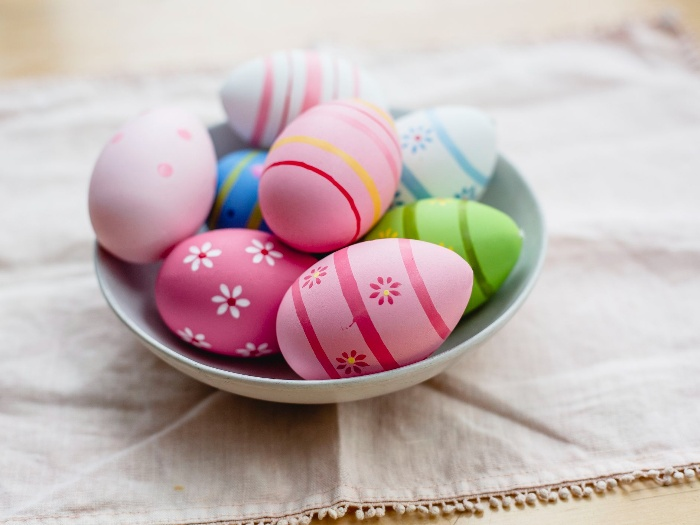colorful easter eggs in a white bowl on a table with a cloth