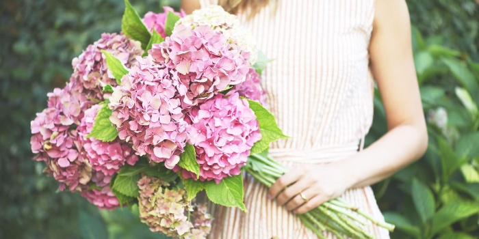 woman in a beige dress holding a large bouquet of pink flowers